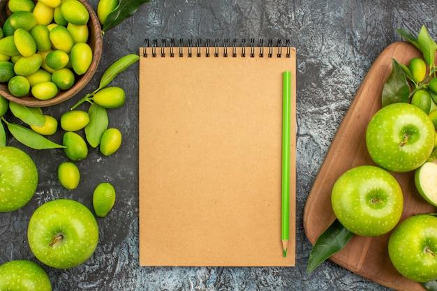 Top vista ravvicinata mele agrumi mele verdi con foglie sulla matita notebook bordo