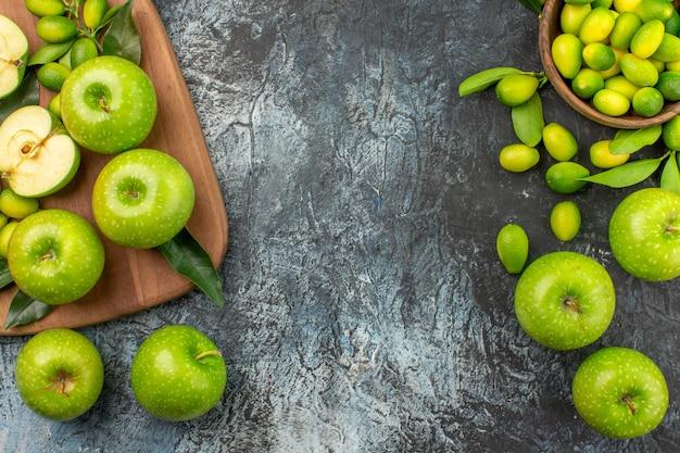 Вид сверху крупным планом яблоки цитрусовые в миске аппетитные яблоки на доске