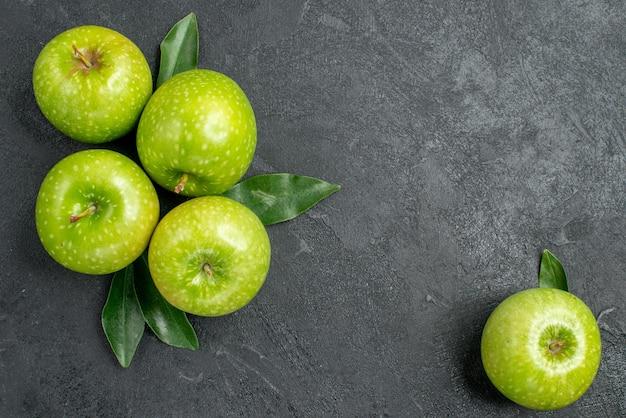 위쪽 클로즈업 보기 사과 어두운 탁자에 있는 사과 옆에 잎이 있는 4개의 녹색 사과