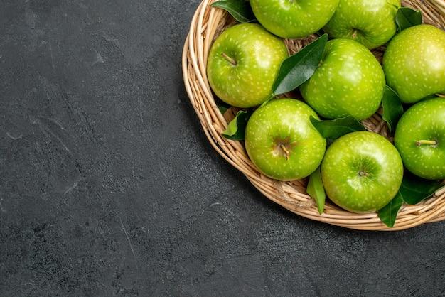 어두운 탁자에 잎이 있는 녹색 사과 바구니 나무 바구니에 있는 위쪽 클로즈업 보기 사과
