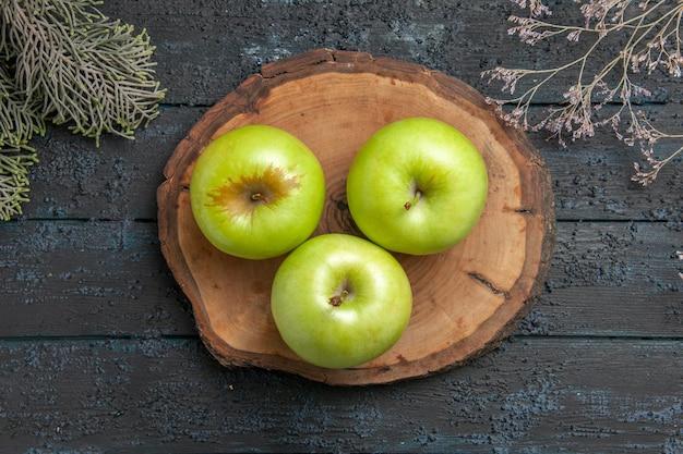 나무 가지 사이의 나무 판자에 있는 녹색 사과 위에 있는 클로즈업 보기 사과