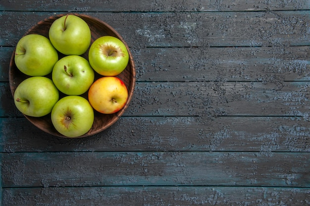 Сверху крупным планом яблоки на столе в миске из семи зелено-желто-красных яблок на левой стороне темного стола