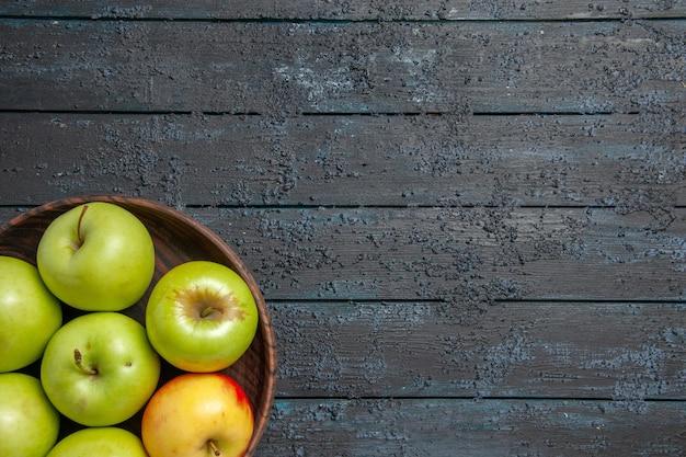 Сверху крупным планом яблоки на тарелке из семи зелено-желто-красных яблок на левой стороне темного стола