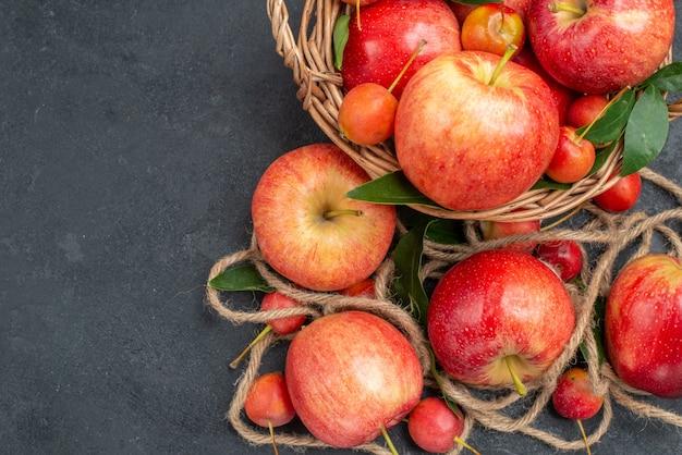 Вид сверху крупным планом яблоки веревка яблоки красно-желтые вишни в корзине