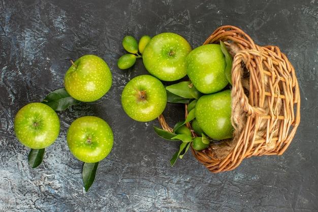 上部のクローズアップビューは、バスケットに葉を持つ食欲をそそる青リンゴをリンゴ