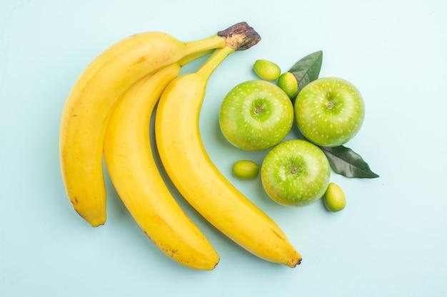 Сверху крупным планом бананы, три красных банана и зеленые яблоки на синей поверхности