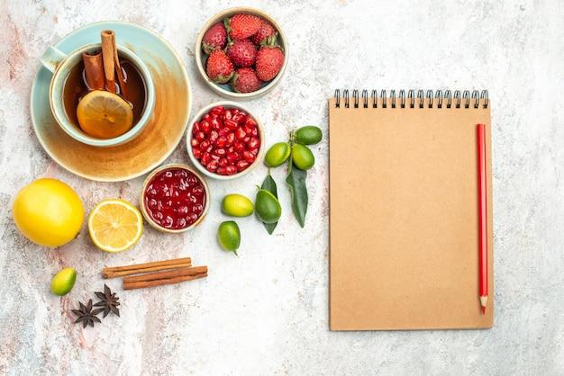 トップクローズアップビューベリーとお茶一杯のお茶柑橘系の果物ベリークッキーノートブックと鉛筆