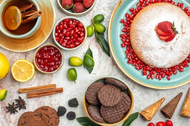 トップクローズアップビューベリーとティーレモンシナモンレモンとお茶のカップベリーとケーキ