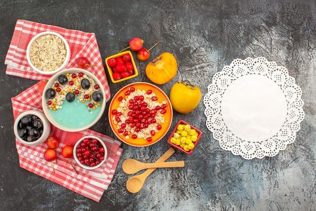 Top vista ravvicinata bacche bacche farina d'avena sulla tovaglia bianco-rosa caramelle gialle centrino di pizzo