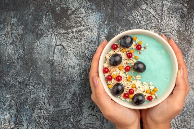 Top vista ravvicinata frutti di bosco ciotola di bacche colorate farina d'avena nelle mani