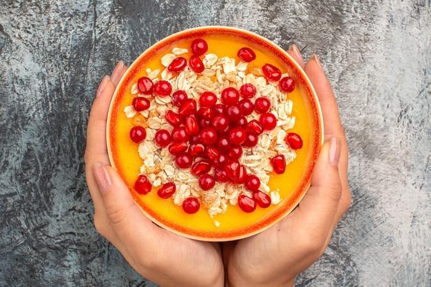 Вид сверху крупным планом ягод миску с зернами граната и овсянкой в руках