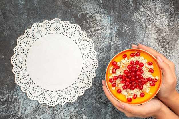 Top close-up view berries bowl of pomegranate seeds oatmeal in the hands lace doily