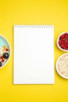 Top close-up view berries bowls of colorful berries oatmeal white notebook