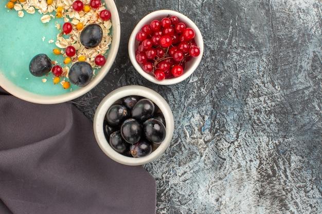 Сверху крупным планом ягоды чаши красной смородины и виноградной овсянки на скатерти