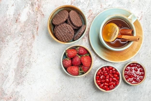 上のクローズアップビューイチゴのベリーボウルザクロの種ザクロの種テーブルの上にレモンとお茶を一杯