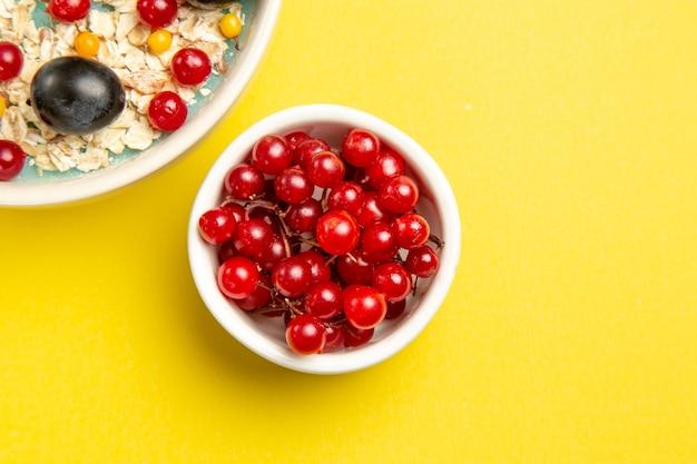 노란색 테이블에 식욕을 돋우는 붉은 건포도의 상위 확대보기 딸기 그릇
