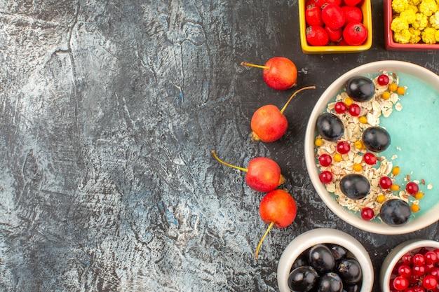 Top vista ravvicinata bacche ciliegia bacche colorate farina d'avena nelle ciotole sul tavolo scuro