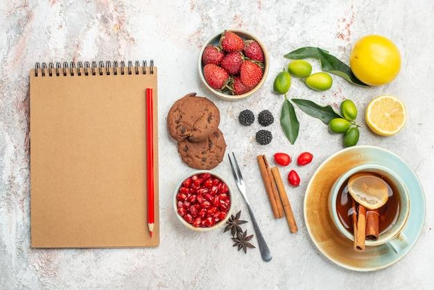 Вид сверху крупным планом ягоды печенье крем блокнот и красный карандаш звездчатый анис печенье клубника белая чашка чая цитрусовые палочки корицы вилка на столе
