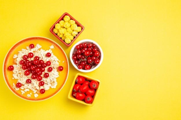 上部のクローズアップビューは、黄色のテーブルにさまざまなベリー黄色いキャンディーオートミールをベリーします