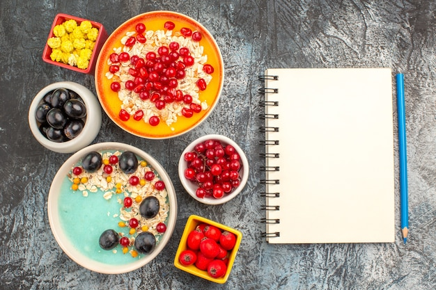 Top close-up view berries grapes cherries red currants pomegranate candies oatmeal notebook pencil