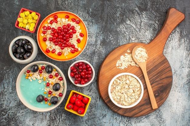 Вид сверху крупным планом ягоды виноград вишня красная смородина гранатовые конфеты овсяные хлопья на доске