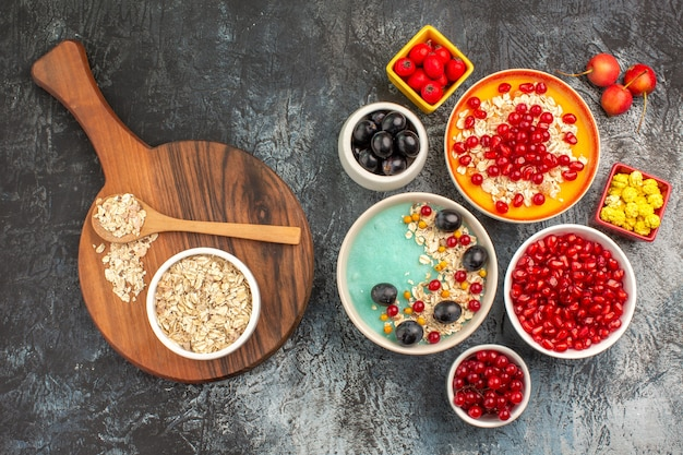 Top close-up view berries grapes cherries red currants pomegranates oatmeal spoon on the board