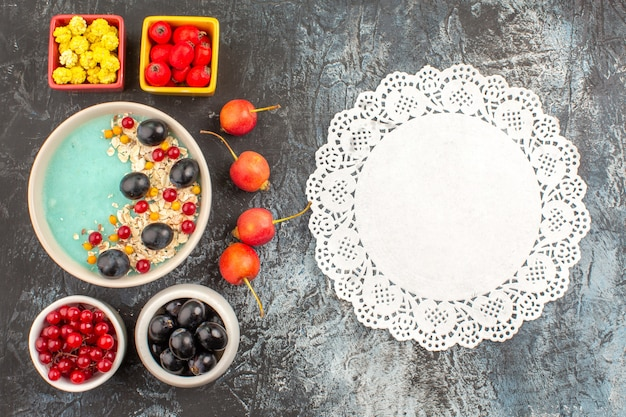 Top close-up view berries lace doily cherry colorful berries oatmeal in the bowls
