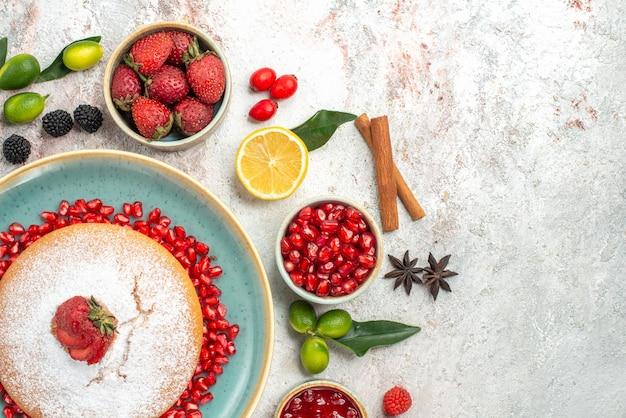 Vista ravvicinata dall'alto bacche di limone bastoncini di cannella marmellata di frutti di bosco la torta con biscotti alle fragole