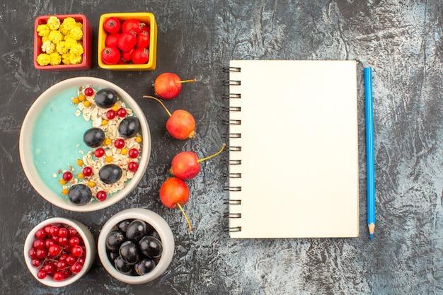 Top vista ravvicinata bacche notebook matita ciliegia bacche colorate farina d'avena nelle ciotole