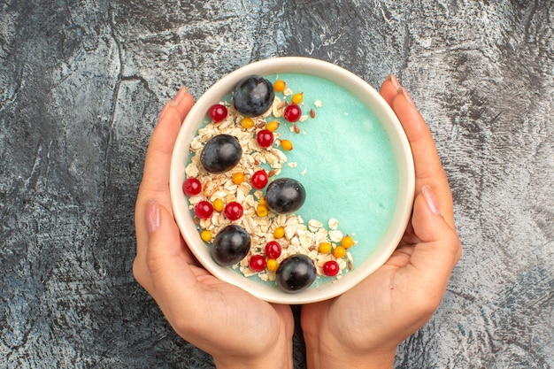 Top vista ravvicinata bacche farina d'avena le appetitose bacche colorate nella ciotola nelle mani