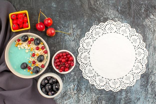 Вид сверху крупным планом ягоды овсянки красочные ягоды граната на скатерти кружевная салфетка