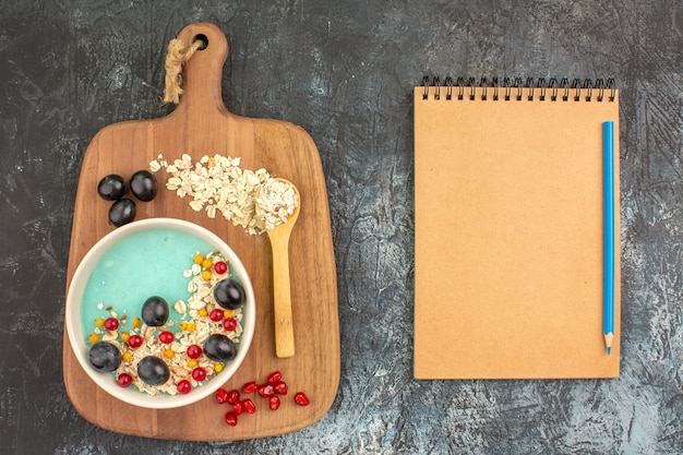 Top close-up view berries oatmeal grapes seeds of pomegranate spoon on the board notebook pencil
