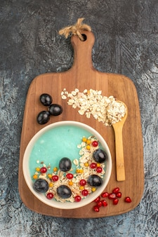 Top close-up view berries oatmeal grapes spoon on the cutting board