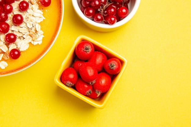 Вид сверху крупным планом ягоды овсянки ягоды красной смородины в мисках