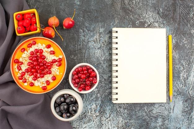Вид сверху крупным планом ягод овсянки с красочными ягодами граната на скатерти тетради
