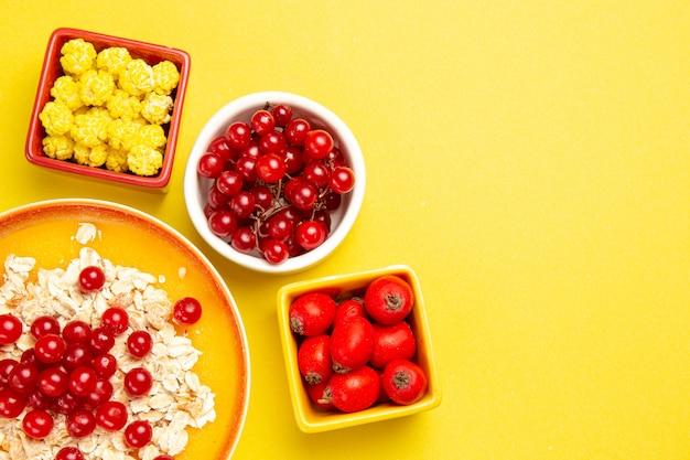 Ягоды овсянки с красной смородиной, ягоды, конфеты на желтом столе