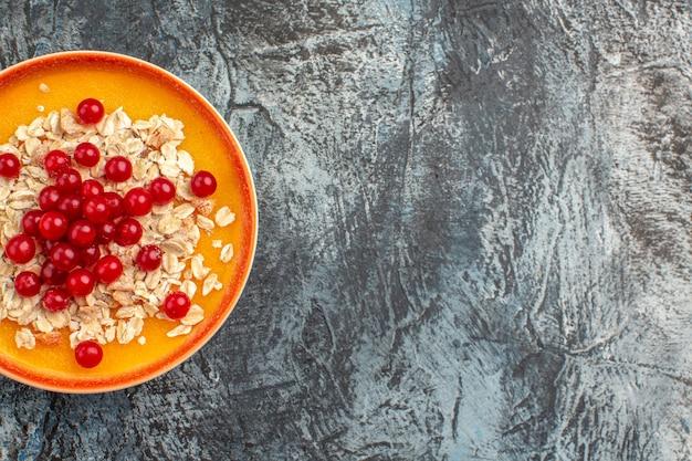 Сверху крупным планом ягоды оранжевая тарелка аппетитной красной смородины на сером столе