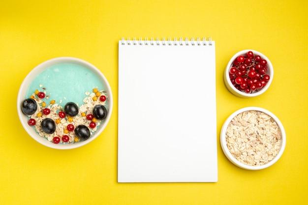 Top vista ravvicinata bacche piatto di bacche colorate farina d'avena ribes rosso in una ciotola bianco notebook