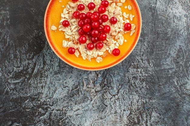 Вид сверху крупным планом ягод тарелку аппетитной красной смородины на сером столе
