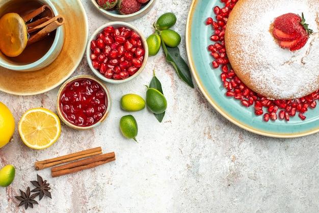 Vista ravvicinata dall'alto bacche e marmellata di tè bacche cannella una tazza di tè la torta con le fragole