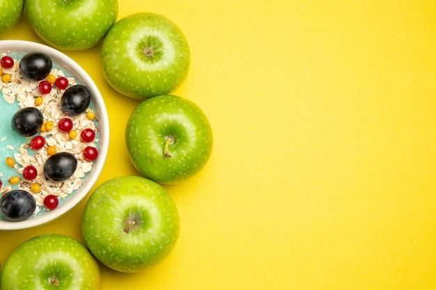 Вид сверху крупным планом ягоды аппетитные ягоды овсяные хлопья в миске зеленые яблоки