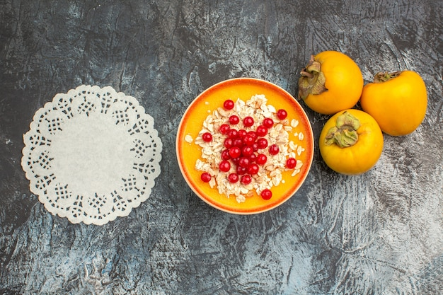 Top close-up view berries three persimmons berries in the bowl lace doily