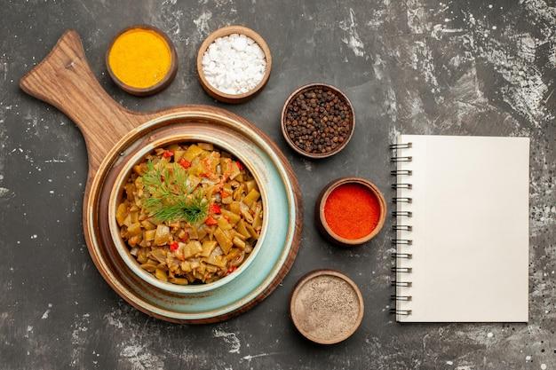 Vista ravvicinata dall'alto ciotola di fagiolini ciotola di fagioli accanto ai cinque tipi di spezie e taccuino bianco sul tavolo nero