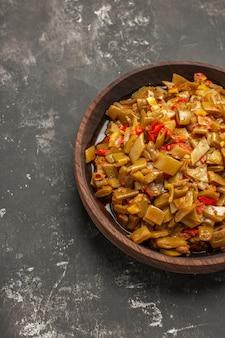 어두운 탁자에 있는 식욕을 돋우는 녹색 콩과 토마토의 식욕을 돋우는 접시 그릇의 상단 클로즈업 보기 그릇