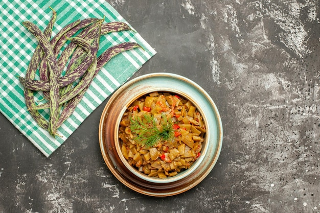 어두운 탁자에 있는 체크무늬 식탁보에 있는 녹색 콩 옆에 있는 녹색 콩 접시와 토마토의 클로즈업 보기 그릇