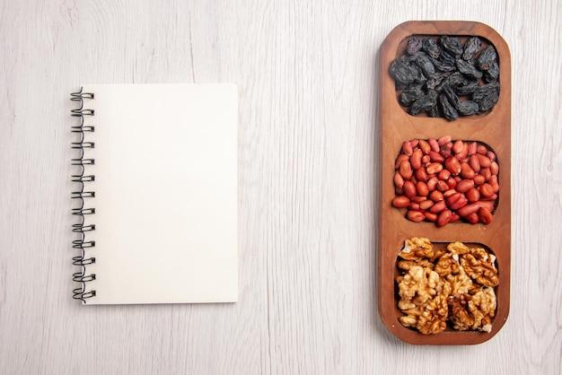 白いテーブルの上の白いノートの横にあるナッツのボウルの上部のクローズアップビューさまざまなナッツのボウル