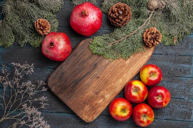 회색 배경에 원뿔이 있는 5개의 사과와 나뭇가지 도마 옆에 있는 잘 익은 석류를 맛있게 먹는 클로즈업 보기 가지와 석류