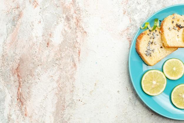 Вид сверху крупным планом на хлеб и лимон, цитрусовые и белый хлеб в тарелке с правой стороны