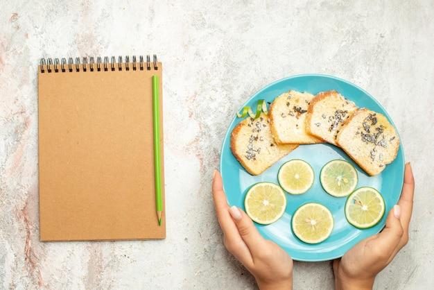 Сверху крупным планом блокнот с хлебом и лимонным кремом и зеленый карандаш рядом с синей тарелкой хлеба и нарезанным лимоном в руке на белом столе