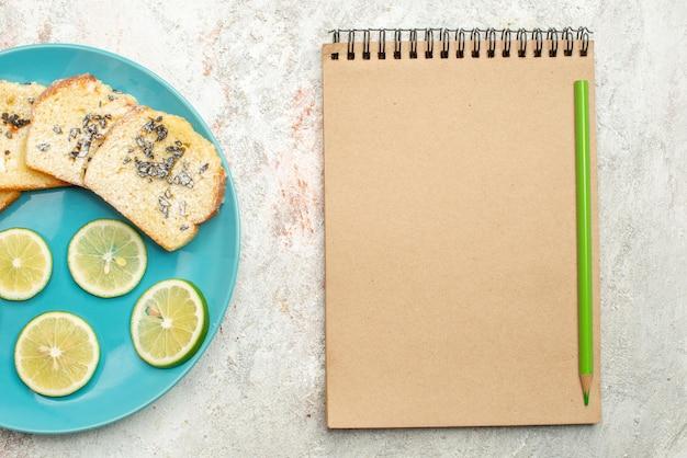 Сверху крупным планом блокнот с хлебом и лимонным кремом и нарезанные зеленым карандашом цитрусовые и белый хлеб в тарелке